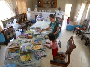 Tarah and her helpers sorting books in Cherangany